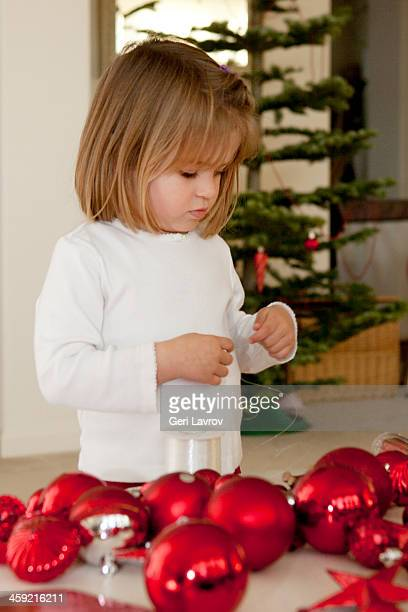 Young girl next to red Christmas ornaments