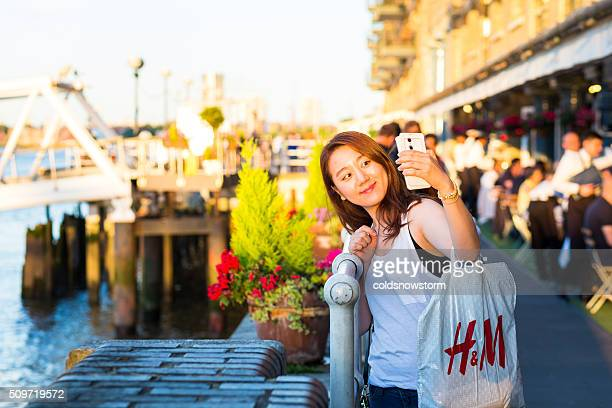 Young girl of Asian ethnicity taking selfie, Southbank, London, UK