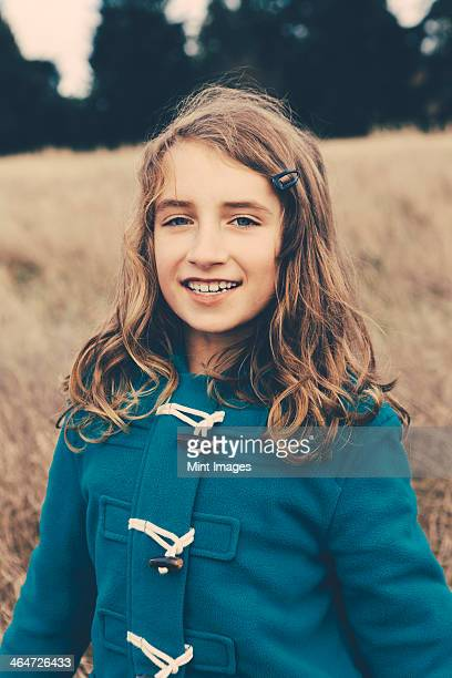 a young girl of nine years old,in a blue duffle coat,smiling at the camera. - 8 9 years stock pictures, royalty-free photos & images