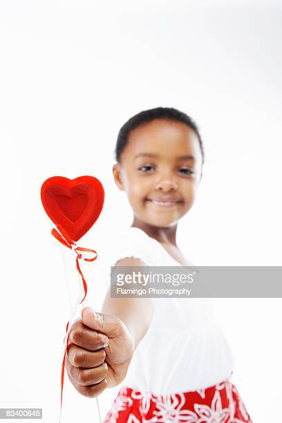 young girl offering heart lollipop - flamingo heart stock pictures, royalty-free photos & images