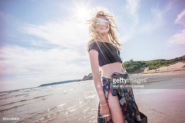 young girl on a beach dancing to music - gower peninsula stock photos and pictures