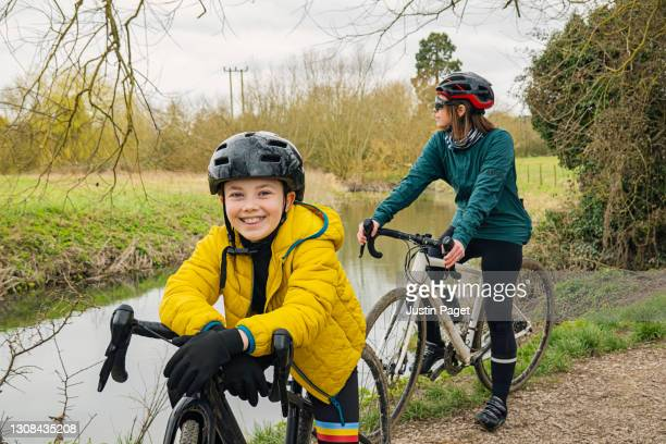 young girl on a bike ride with her mother - non urban scene stock pictures, royalty-free photos & images