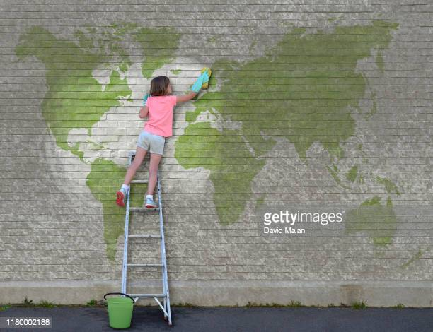 a young girl on a ladder, who has started cleaning a world map mural. - environmental issues imagens e fotografias de stock