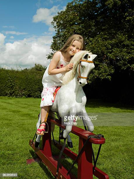 A young girl on a rocking horse
