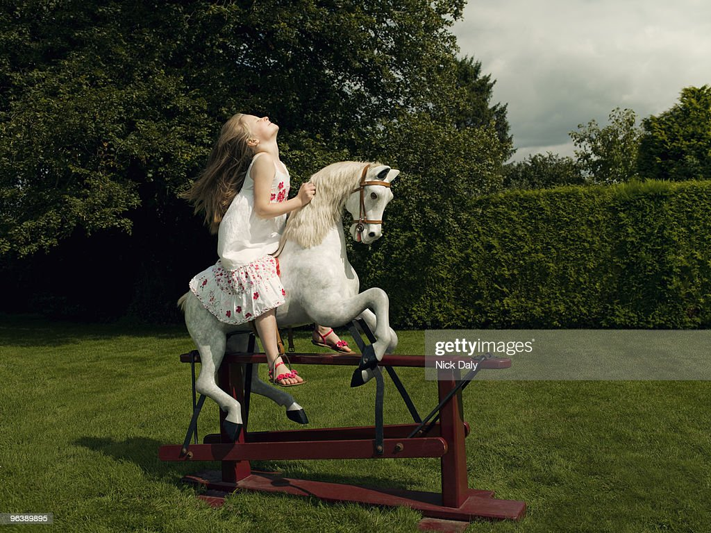 A young girl on a rocking horse : Stock Photo