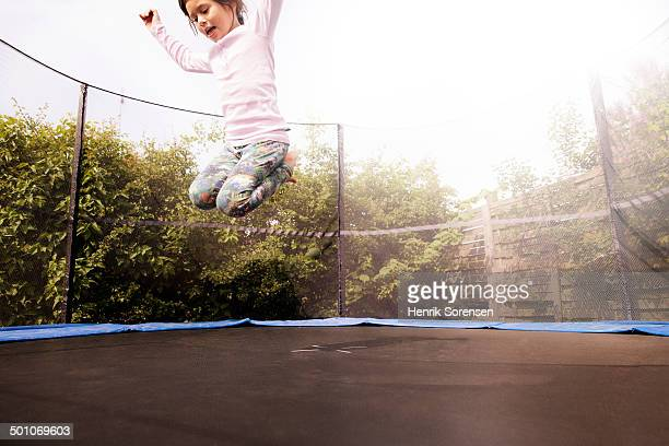 young girl on a trampoline in a garden