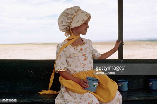 A young girl on a vacation designed to simulate the experience of pioneers on the Oregon Trail wears a costume of the style worn by pioneer girls...