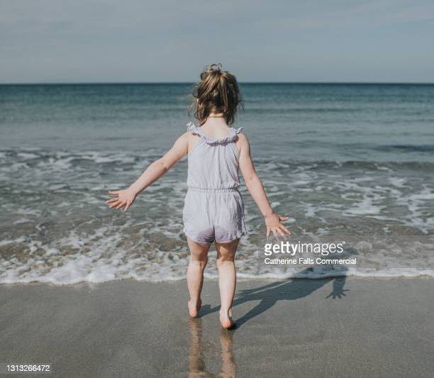 young girl on a wet beach runs towards the ocean - horizon over water stock pictures, royalty-free photos & images