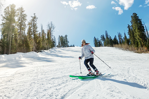 Young girl on alpine skiing on a snowy track against the sky 880950908
