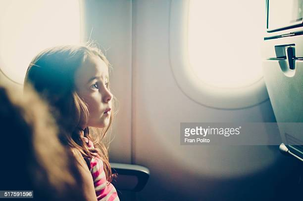 Young girl on an airplane watching tv.