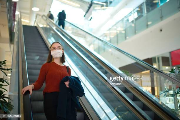 young girl on an escalator in shopping mall wearing medical mask to protect herself against virus or pollution - shopping centre stock pictures, royalty-free photos & images