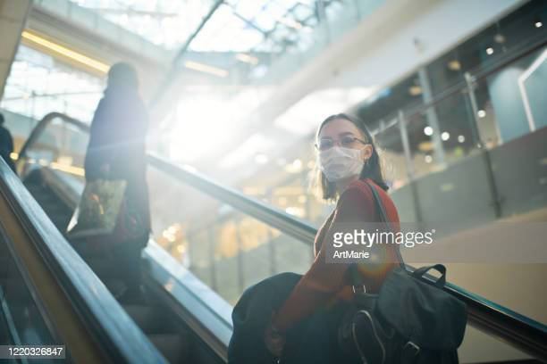 young girl on an escalator with social distancing in shopping mall wearing medical mask to protect herself against virus - railway station stock pictures, royalty-free photos & images