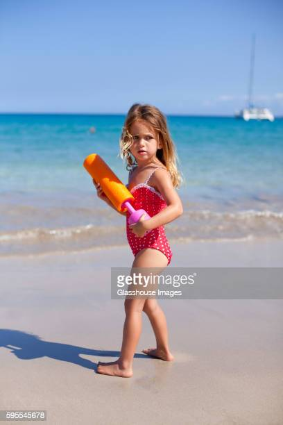 Young Girl on Beach With Squirt Gun