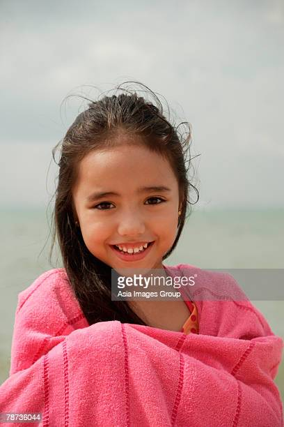 Young girl on beach wrapped in pink towel, smiling