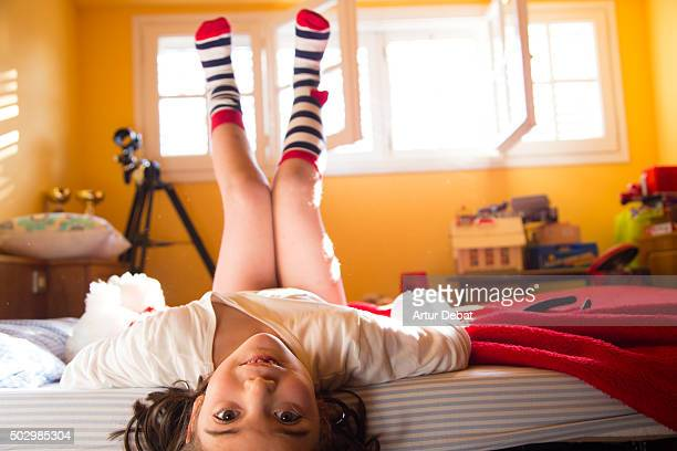 Young girl on bed on morning sunrise light with colorful socks.