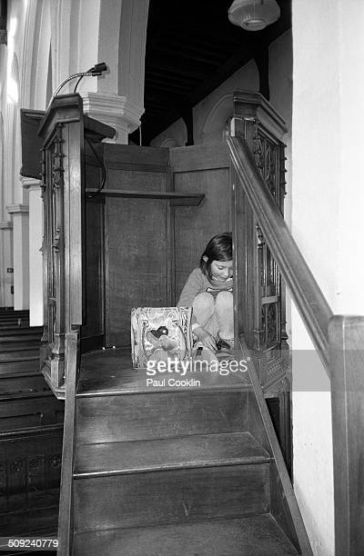 Young girl on church pew looking at mobile tablet