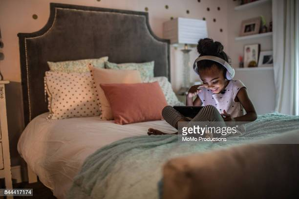 young girl (6yrs) on couch using tablet - digital native stock pictures, royalty-free photos & images