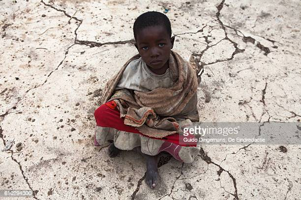 young girl on cracked concrete in malawi (2016) - hongerig stockfoto's en -beelden