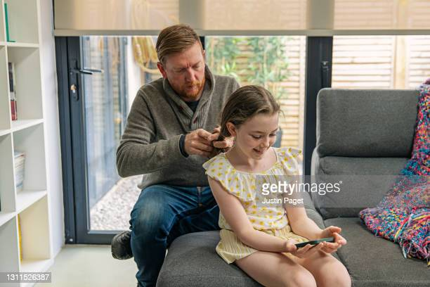 young girl on her smartphone whilst her father sorts her hair - genderblend stock pictures, royalty-free photos & images