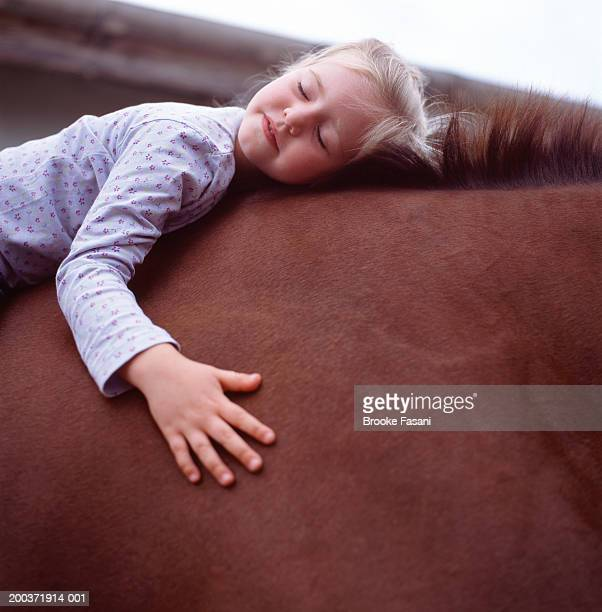 Young girl (4-6) on horse with eyes closed