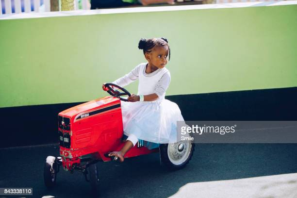 Young girl on miniature toy tractor