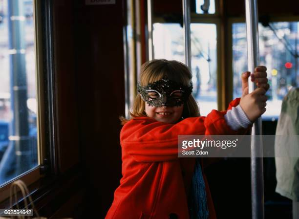 young girl on new orleans streetcar wearing mardi gras mask - mardi gras girls stock photos and pictures