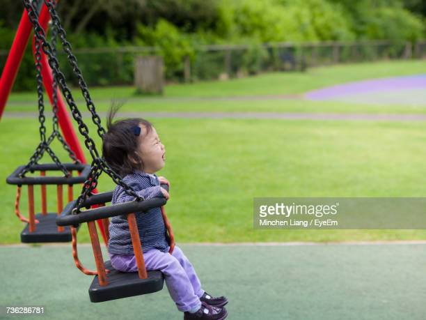 Young Girl On Swing At Park