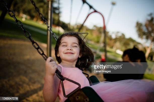 young girl on swing, closing eyes and smiling - parte del cuerpo animal fotografías e imágenes de stock