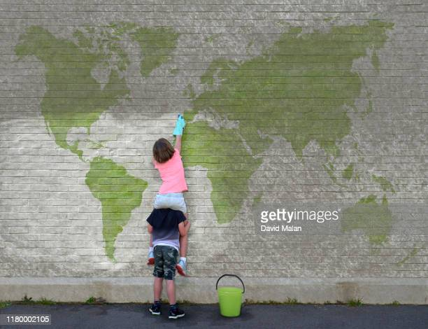 a young girl, on the shoulders of a young boy, cleaning dirt off a world map mural. - carbon footprint stock pictures, royalty-free photos & images