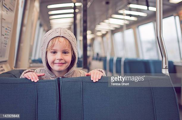 Young girl on train peeking over seats