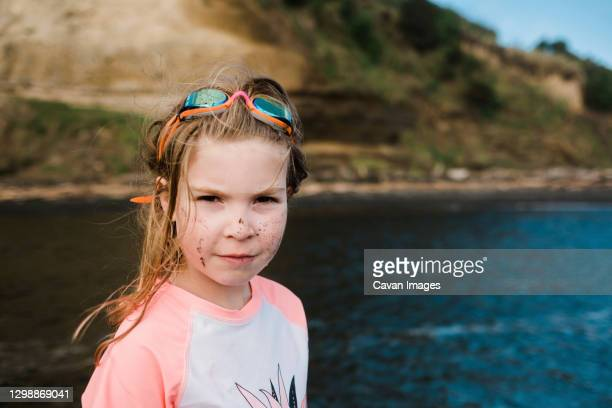 young girl on waters edge wearing rashie and googles - google stock pictures, royalty-free photos & images
