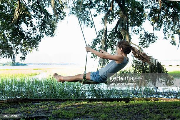Young girl on wooden swing in garden