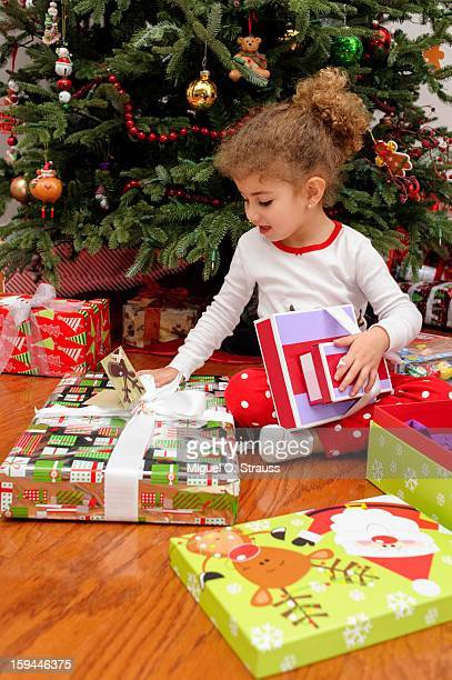 Young girl opens gifts on Christmas morning
