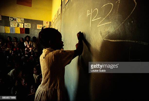 A young girl orphaned when her parents died of AIDS writes on a wall that doubles as a blackboard in the community school Seventy percent of the...