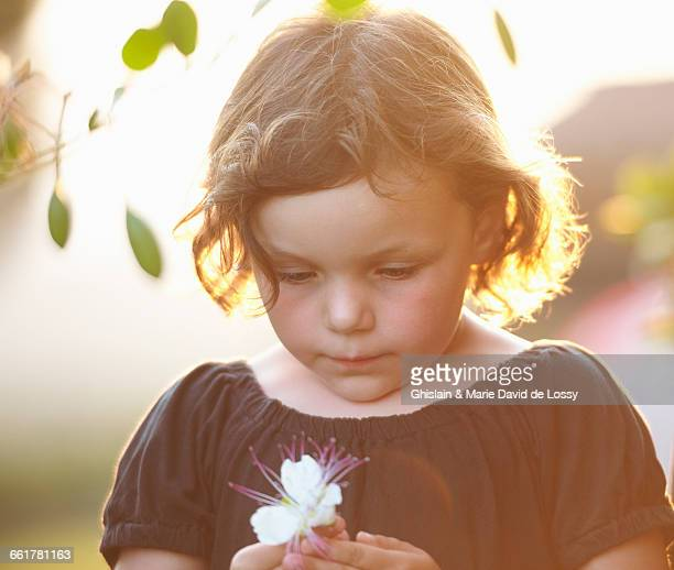 Young girl, outdoors, holding flower
