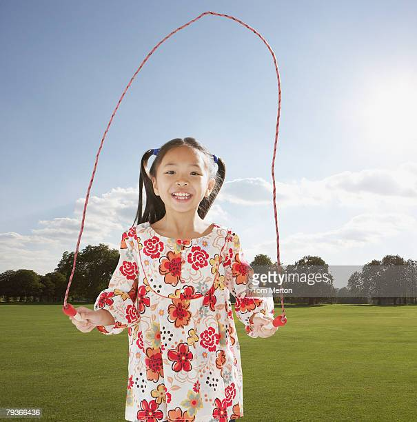 young girl outdoors jumping rope - skipping along stock pictures, royalty-free photos & images