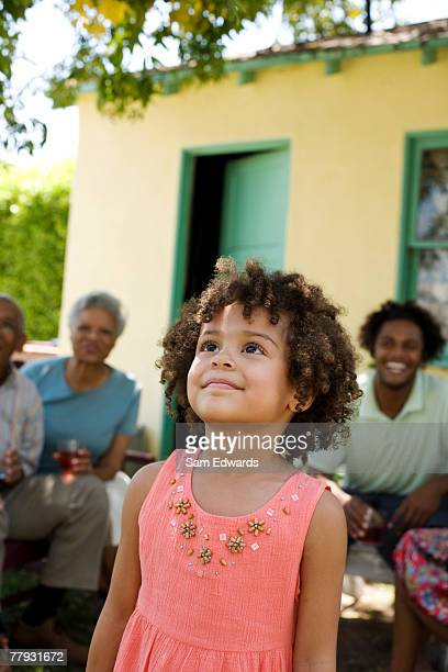 young girl outdoors looking up with people in background - african american man helping elderly stock pictures, royalty-free photos & images