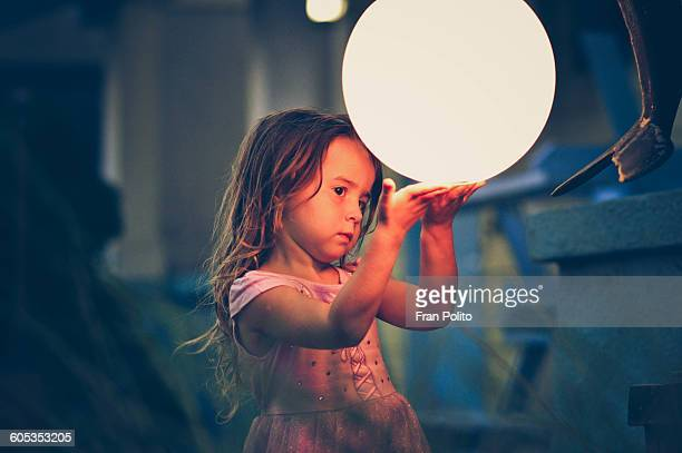 Young girl outside playing with a glass ball.