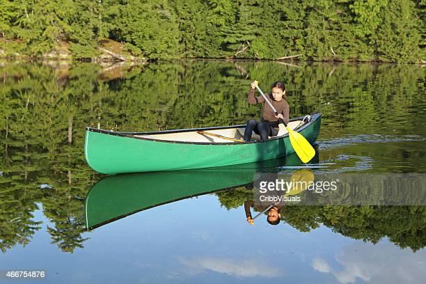 Young girl paddling a canoe on a lake