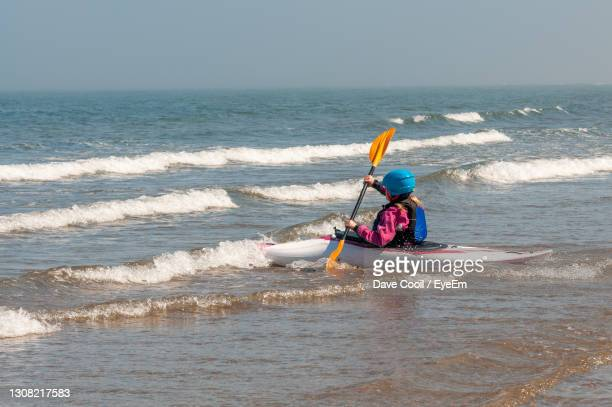 young girl paddling kayak through surf out towards the sea on a sunny day - human age stock pictures, royalty-free photos & images