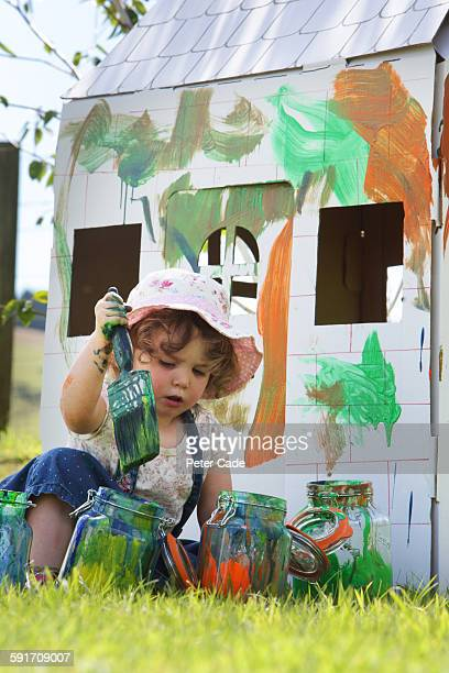Young girl painting cardboard house