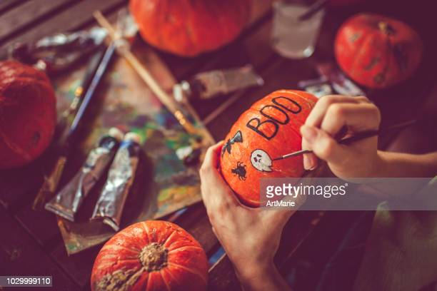 young girl painting on pumpkin in halloween - pumpkin stock pictures, royalty-free photos & images