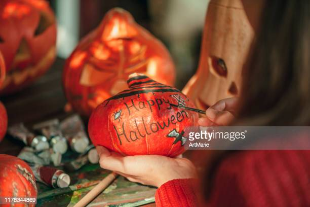 young girl painting on pumpkin in halloween - carving craft product stock pictures, royalty-free photos & images