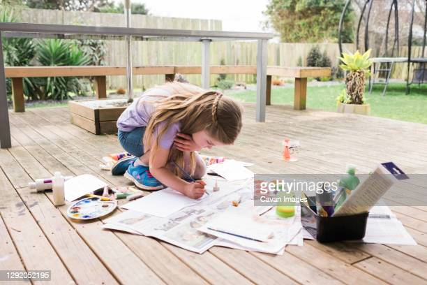 young girl painting outside on a wooden deck - garden drawing stock pictures, royalty-free photos & images