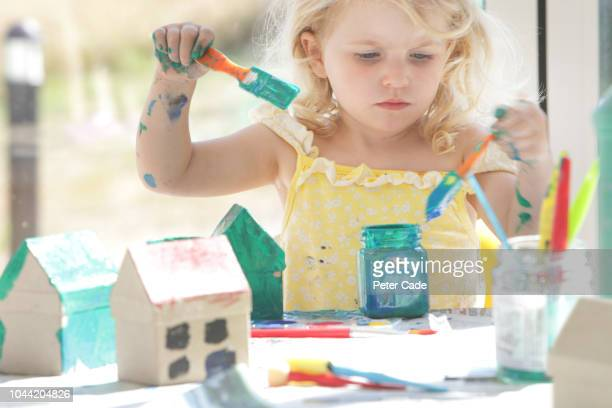 young girl painting small cardboard houses - nursery school child stock pictures, royalty-free photos & images