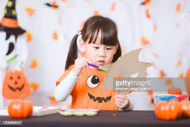 young girl painting witch mask for halloween party at home - cute stock pictures, royalty-free photos & images