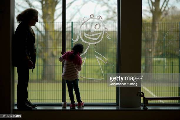 A young girl paints a picture of herself on the school window as children of key workers take part in school activities at Oldfield Brow Primary...