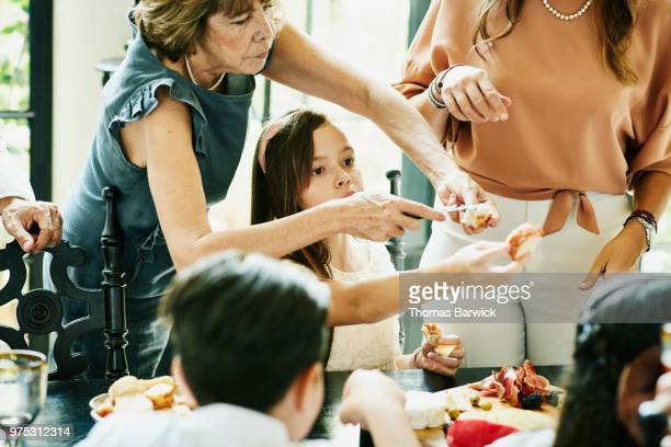 Young girl passing bread while family shares appetizers during dinner party