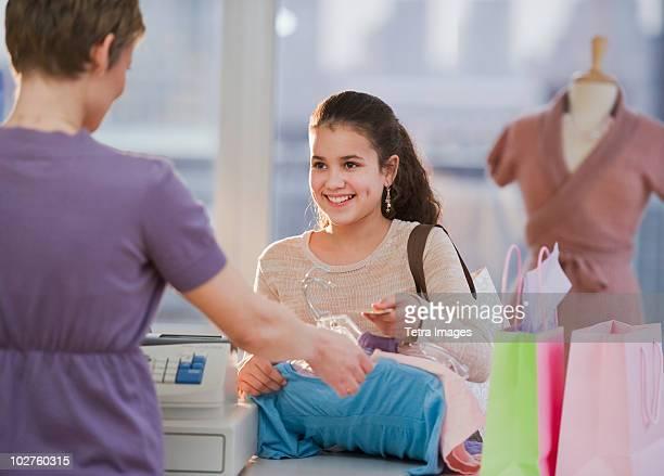 young girl paying for clothing - damkläder bildbanksfoton och bilder