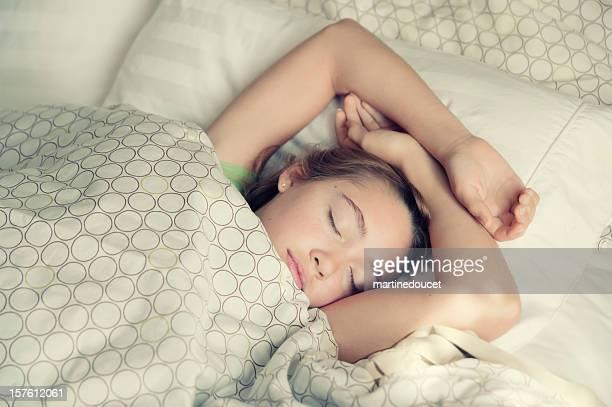 Jeune fille dormir paisiblement en lumière les draps.